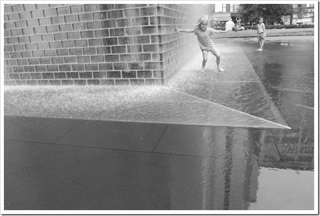 Rodney Daly, girl playing in water on the street