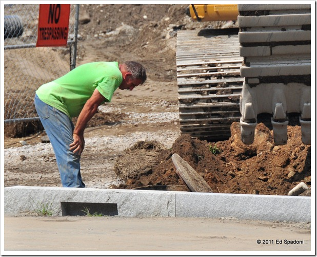 Man looking in hole at a construction site