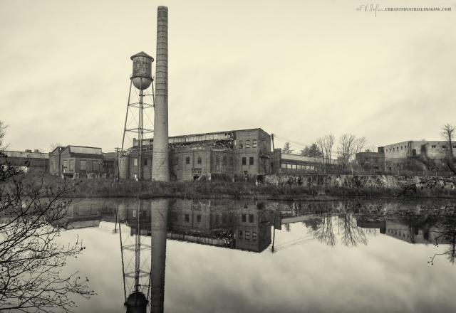 """One day I rerouted to work due to heavy traffic and I """"discovered"""" this fantastic site.  I've been back twice since and photographed the plant on the river.  This was once the Michelin Tire Factory, originally built in 1907.  Michelin abandoned the factory during the Depression in 1930, and it has stood empty since.  Although the site itself is closed to the public (it will eventually be razed), one can still get a great view across the river.  The water tower and smokestack are quite impressive and are what drew me to the site in the first place."""