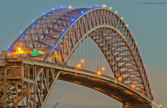 """Simply put, the Bayonne Bridge at twilight.  The lights are on, in red, white and blue.  This was shot with a long zoom (28-300mm) from the corner of 1st St and Ave A.  I grew up in Bayonne,  and some of my earliest memories are centered there.  This is my favorite bridge, and I've shot it a number of times, both on and beneath it.  If this bridge looks familiar, it's probably because the Bayonne Bridge was prominently featured in Steven Spielberg's remake of """"War Of The Worlds"""" starring Tom Cruise."""