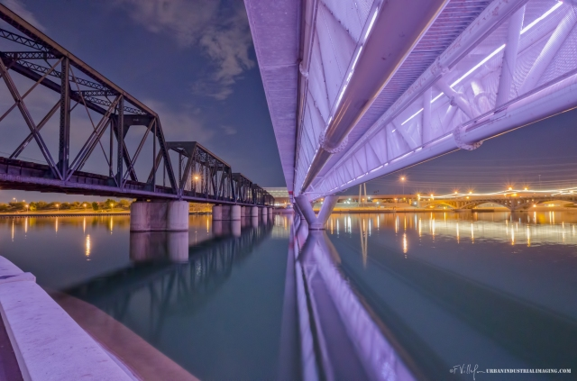 """On our trip to AZ, my fiancé and I had dinner at a restaurant in Tempe one evening.  Wanting to find something notable to photograph, we queried our waiter as to where we could go to see something """"notable"""".  He directed us to Tempe Town Lake to the lighted railroad bridge.  2012 was Tempe's centennial year, and they happened to be celebrating by lighting the bridge every evening at the prestigious Town Lake (a man-made lake, as all bodies of water in Phoenix are usually dry).  Notice that the original Train Trestle was build in 1912, and the remnant of the original is still standing next to the modern bridge.  This shot got me hooked on nighttime photography."""