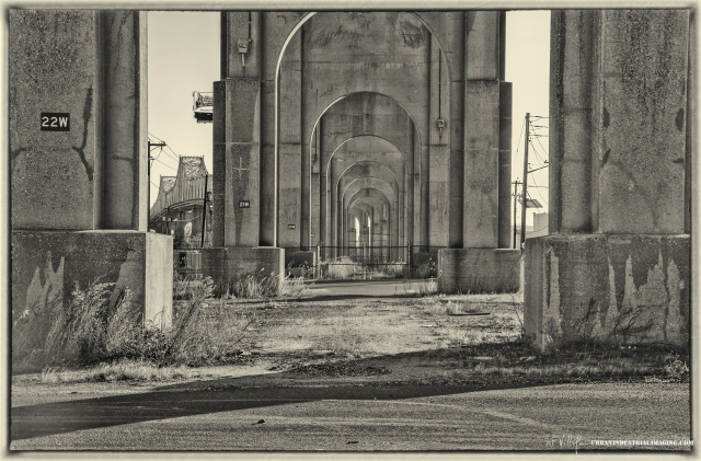 """This is one of the earliest bridge shots from my """"Port Authority"""" series.  It was taken from beneath the OuterBridge crossing which connects Perth Amboy, NJ to Staten Island, NY.  The composition features the arches in a geometrically diminishing pattern, with the bridge itself """"peeking"""" from between two of the columns.  I converted to black and white to give it a """"gritty"""" industrial look.  I was fortunate that no security stopped me, given the Post 9/11 threat of terrorism.  A suggestion to those wishing to capture these types of scenes – bring samples of your work with you in the event you are stopped and questioned.  Pictures DO speak a thousand words."""